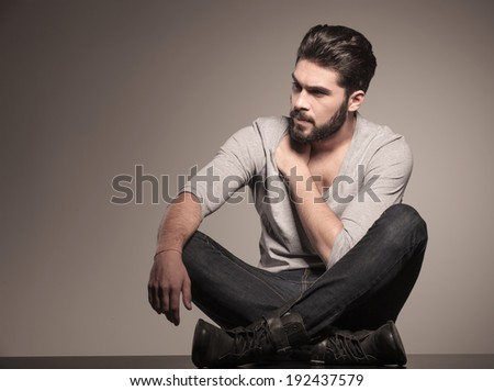 fashion man looking to his side and sits down on the floor  - stock photo