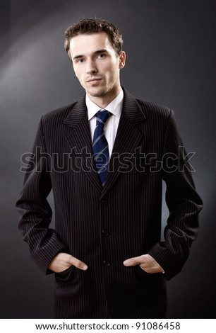 Fashion man portrait, handsome male model in suit and hands in pockets, studio shot on dark background - stock photo