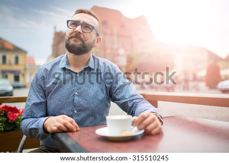 Fashion man sitting in a cafe at market square in sunset. - stock photo