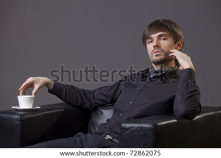 fashion man sitting in chair with cup coffee