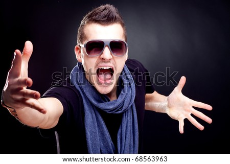 fashion man wearing a blue scarf and sunglasses screaming on a dark background