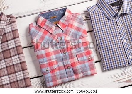 Fashion men's checkered shirt on white wooden background. - stock photo