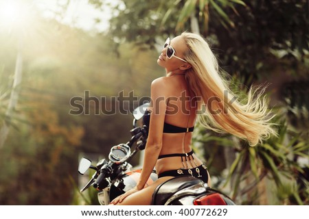 Fashion model biker girl on a motorcycle - stock photo