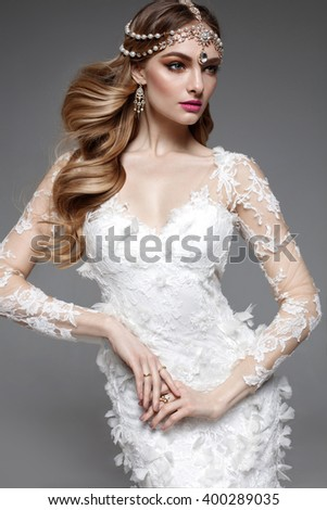 Fashion model bride with long flowing blonde hair and make up. Studio shot. Wedding dress. Pink lips. Jewelry. Middle east style woman. - stock photo
