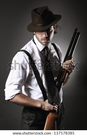 Fashion model dressed like a gangster poses with shotgun and hat .Grey backdrop portrait