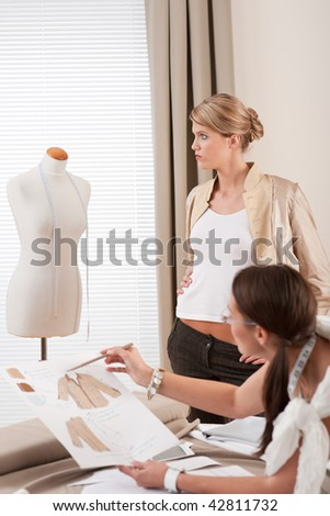Fashion model fitting clothes by professional designer studio