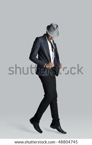 Fashion model floats off the ground in his suit - stock photo