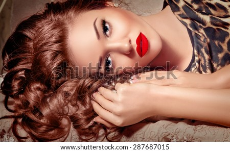 Fashion Model Girl Face Portrait with Hands touching Curly Hair, Beauty Woman Make up, Long Lashes, Blue Eyes, Red Sexy Lips, Makeup Closeup, Perfect skin, French Manicured nails, Luxury make-up. - stock photo