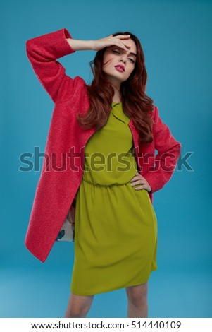 Fashion Model Girl In High Fashionable Clothing Posing On Blue Background. Beautiful Sexy Woman With Perfect Makeup And Elegant Hairstyle Wearing Trendy Clothes, Green Dress, Stylish Dark Pink Coat