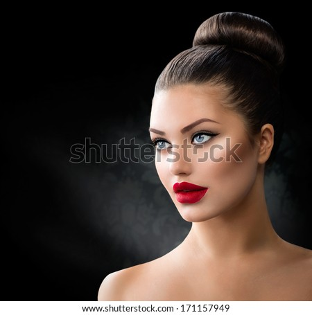 Fashion Model Girl Portrait with Blue Eyes and Full Sexy Red Lips. Creative Hairstyle. Hair Bun. Hairdo. Make up. Beauty Woman isolated on a Black Background  - stock photo