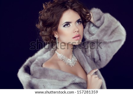 Fashion Model Girl Portrait with jewelry wearing in grey mink fur coat isolated on black background. - stock photo