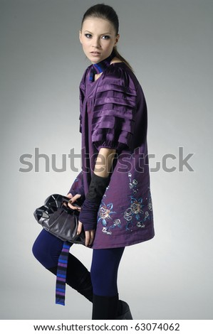 fashion model holding little purse in light background - stock photo