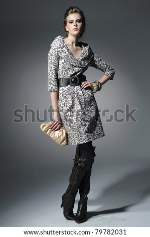 fashion model holding little purse posing in light background - stock photo