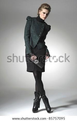 fashion model holding little purse posing on light background - stock photo