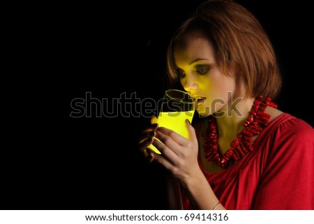 fashion model holding up a glass of glowing liquid