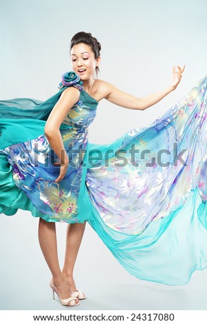 Fashion model in a beautiful turquoise dress - stock photo