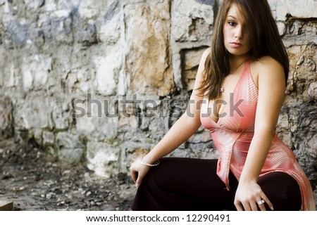 Fashion model in an against spray paint graffiti on a stone wall background