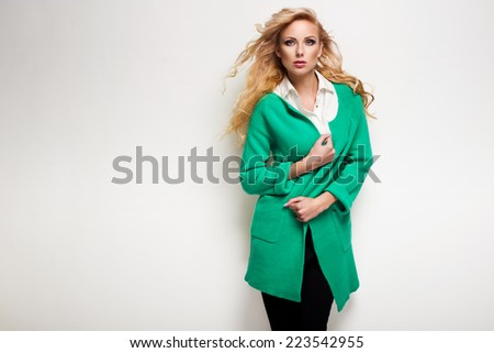 Fashion model in autumn clothes posing in the studio - stock photo