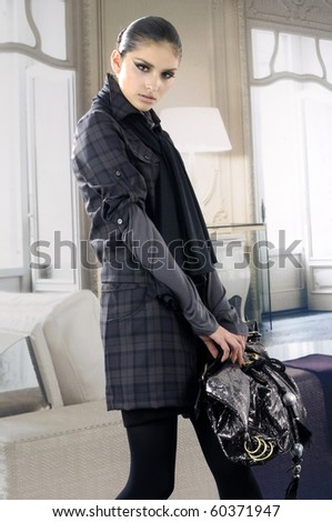 fashion model in autumn/winter clothes holding handbag posing in the studio - stock photo