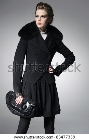 fashion model in autumn/winter clothes holding little purse posing gray background - stock photo