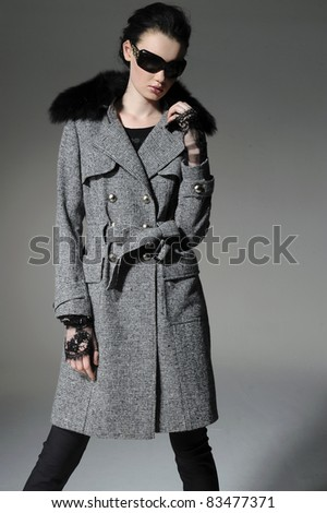 fashion model in autumn/winter clothes wearing sunglasses posing gray background