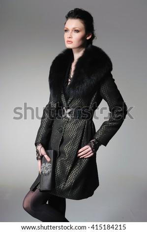 fashion model in black coat clothes posing in studio - stock photo