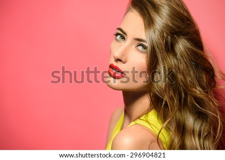 Fashion model in bright yellow dress posing over pink background. Beauty, fashion concept. Hair, healthy hair.   - stock photo