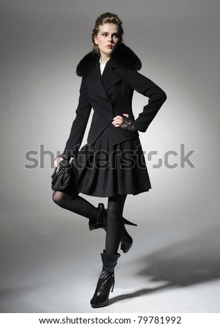 fashion model in coat clothes posing in light background - stock photo