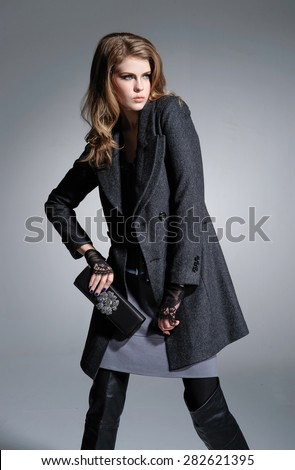 fashion model in coat holding little purse posing on light background - stock photo