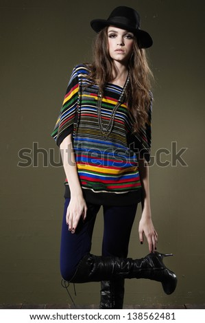 Fashion model in colorful dress in hat on dark background