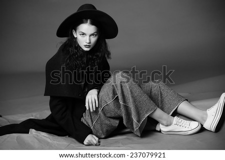 Fashion model in design clothes a posed on gray background - stock photo