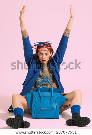 Fashion model in design clothes and  bag posed on light color background - stock photo