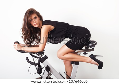 fashion model in elegant dress and high heel shoes on a training bike white background
