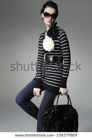 fashion model in fashion dress with handbag posing on gray background - stock photo