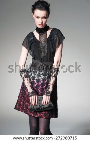 fashion model in fashion dress with scarf holding purse in the studio - stock photo