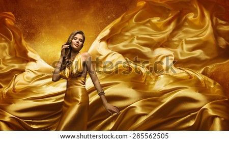 Fashion Model in Gold Dress, Beauty Woman Posing over Flying Waving Cloth, Girl with Yellow Dynamic Silk Fabric - stock photo
