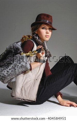 fashion model in modern clothes with hat sitting in studio