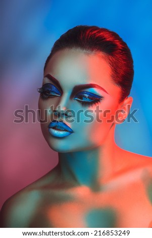 Fashion model in red and blue lights with healthy skin and makeup in studio