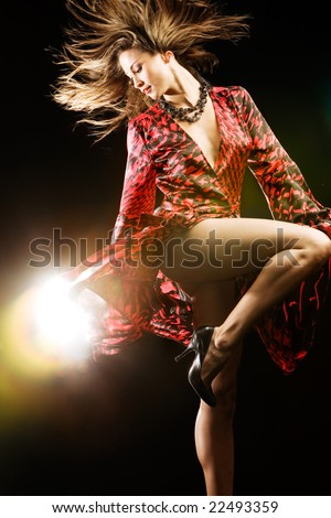 Fashion model in red dress on black studio background