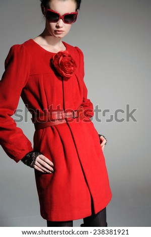 fashion model in red dress posing on gray background - stock photo