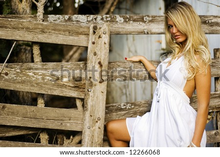 Fashion model in sexy white dress shot around the barn on the farm