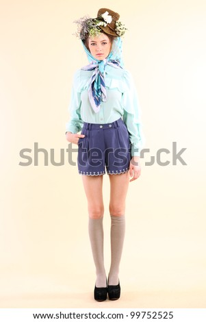 Fashion model in spring light blue and purple clothes on beige background.