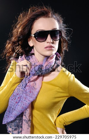 fashion model in sunglass ,scarf posing-black background - stock photo