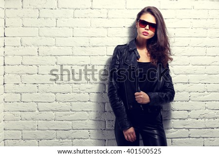 fashion model in sunglasses, black leather jacket, leather pants. Posing near white brick wall. - stock photo
