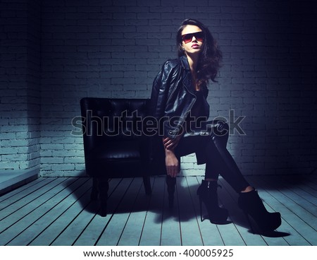 fashion model in sunglasses, black leather jacket, leather pants. Sitting in vintage leather armchair.