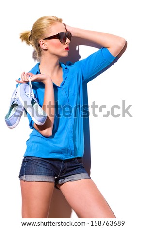 Fashion model in sunglasses holding sneakers and looking away. Three quarter length studio shot isolated on white. - stock photo