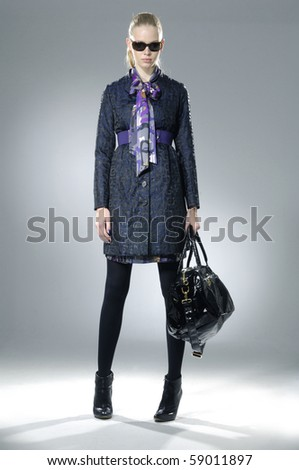 fashion model in sunglasses with bag posing at light background