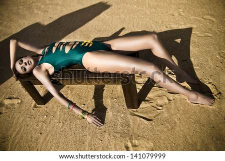 Fashion model in swimsuit posing at the beach on sand - stock photo