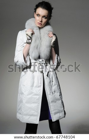 fashion model in winter fur coat clothes posing at light background - stock photo