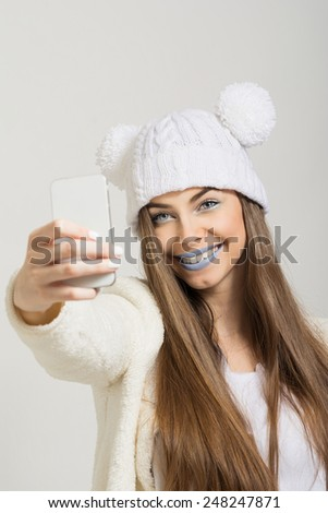 Fashion model in winter style taking a selfie with smartphone. Beautiful young woman with white beanie hat and blue lips photographing herself with cellphone smiling. No filter, medium retouch. - stock photo